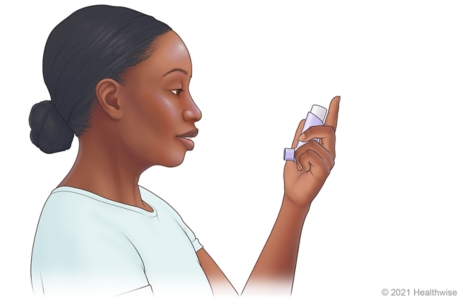 Person holding inhaler upright, with mouthpiece on bottom facing mouth.