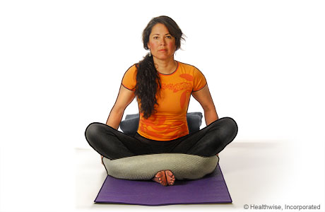 Picture of a woman in step three of reclining bound angle yoga pose