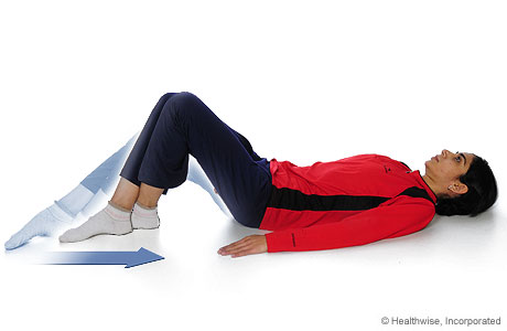 A woman doing the knee-flexion-with-heel-slide exercise